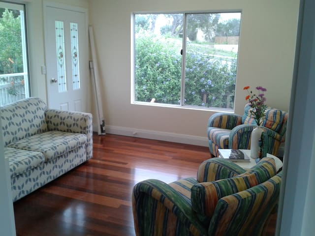 Sun room with sofa bed, breakfast table and television