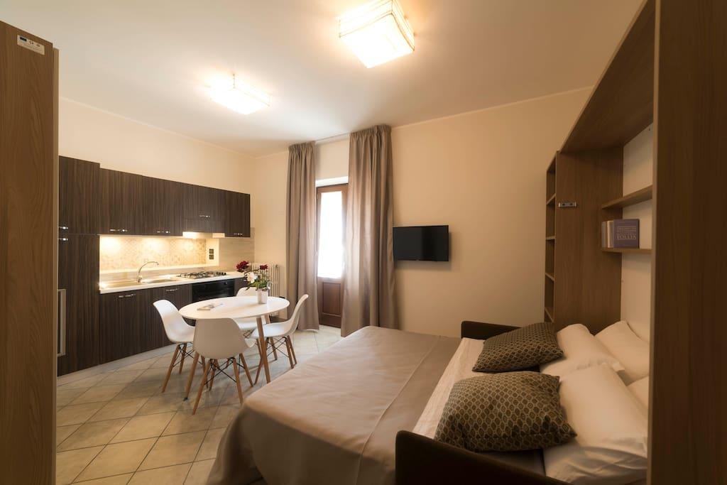 Bilocale: vista della camera principale con il letto aperto e cucina