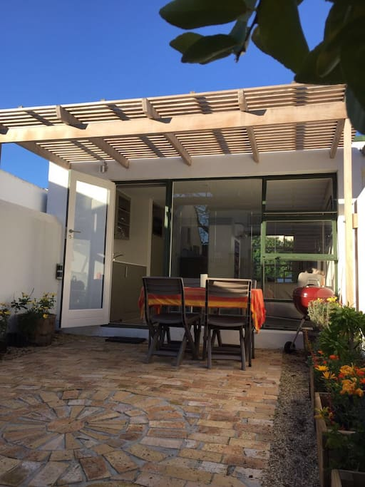 Private courtyard, patio with outdoor table and 4 chairs, Weber braai|grill and cooking tools, garden with colourful waterwise indigenous plants|flowers.