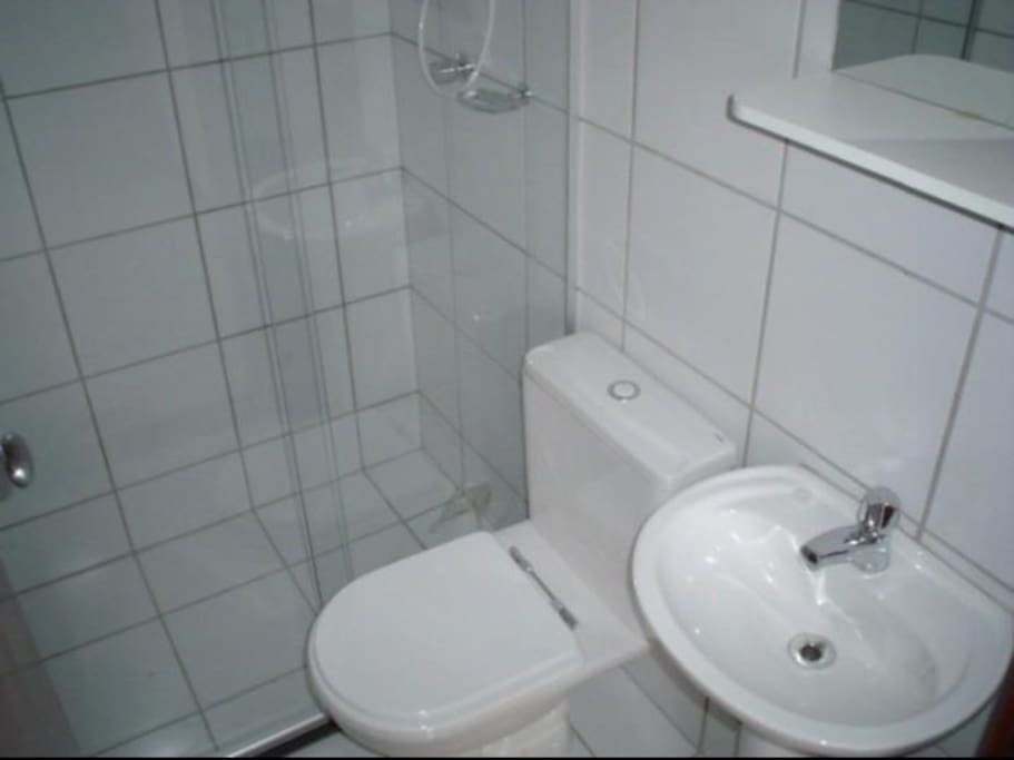 Banheiro com box em vidro temperado.