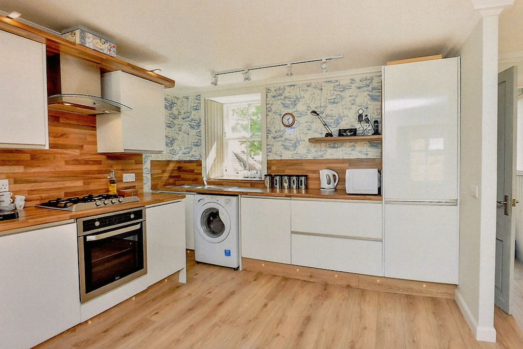 Kitchen end of open plan room. Includes dishwasher and washing machine.