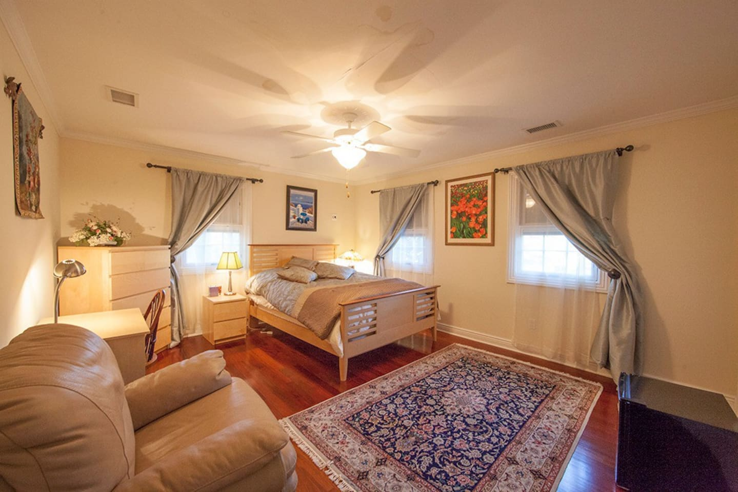 Sunny, spacious bedroom with a queen size bed, office area, walk in closet