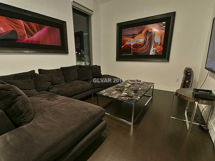 "Lounge room with 70"" TV and black velvet sofa."