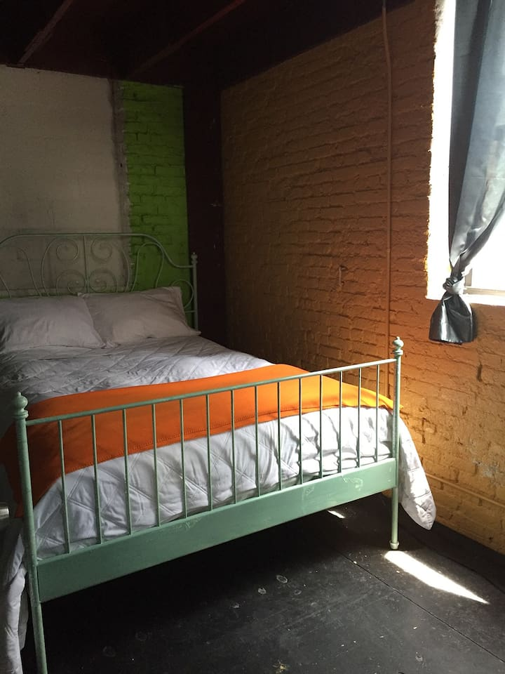 Queen Bed in Small Room with Exposed Brick