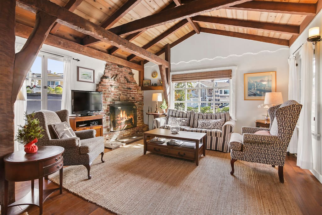 Living area with vaulted ceilings, wood beams, and original stone fireplace.