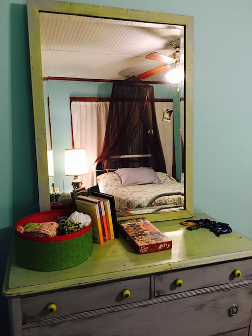 Dresser mirror with the reflection of the double bed in the teal room.  Ceiling fan  and a small desk with chair are in this bedroom.