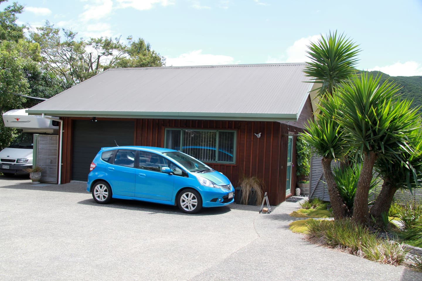 At the end of the tarsealed driveway, veer to the right to park (where the blue car is in the photo), outside your studio.  Your entrance door can be seen through the open gate.  Our house is separate and off to the right up a short cobbled path.