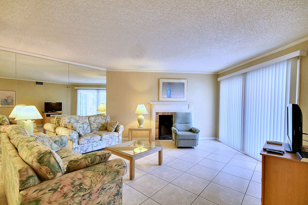 """Sunny and spacious living room with fireplace, queen-size sofa bed and 32"""" TV."""