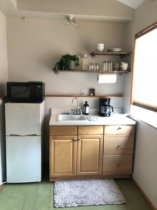 Kitchen with full fridge, microwave, hot plate, coffee make & utensils