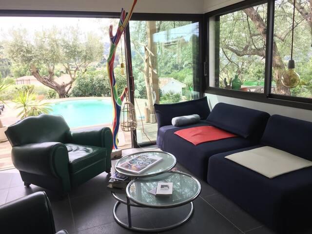 Un salon spacieux et confortable avec de grandes baies vitrées donnant sur la terrasse