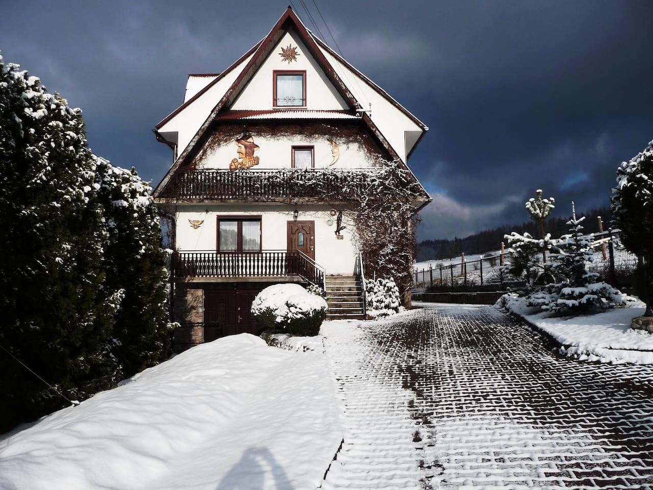 Dom Sosenek zimą. Strona wschodnia budynku z parkingiem i podjazdem.