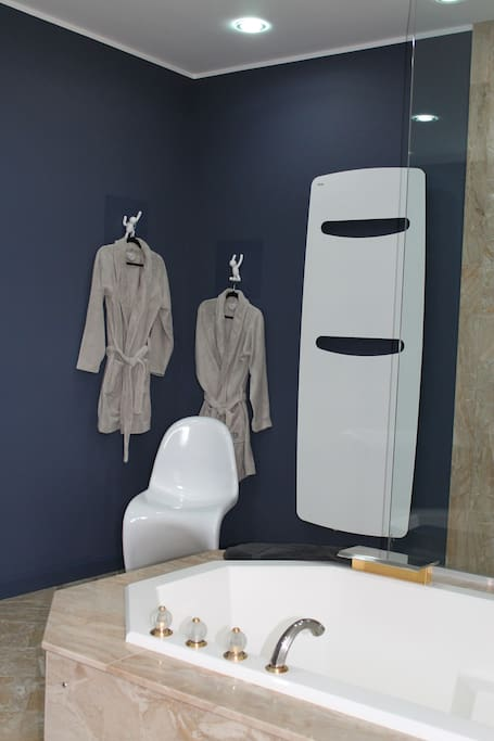 grande salle de bain équipée de baignoire et douche