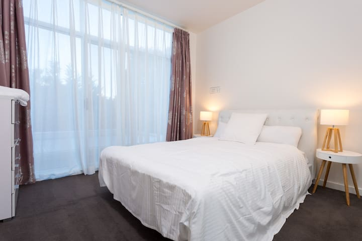 A third bedroom faces the garden and comes furnished with a queen bed, quality linen and bedside tables