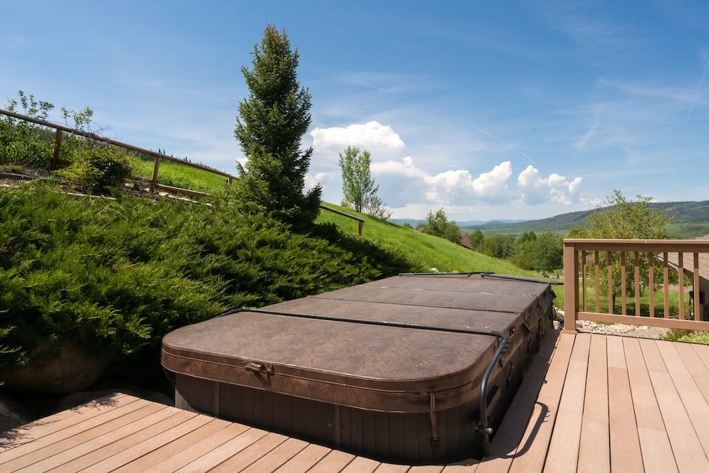 Enjoy a soak in the private 10-person hot tub overlooking the verdant landscape.