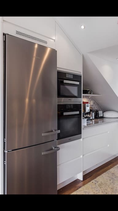 A fully equipped kitchen with an extra large  refrigerator,  oven, microwave and toaster.