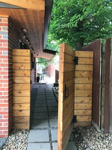 Your entry gate and private side yard with cute lighting and a couple of chairs.