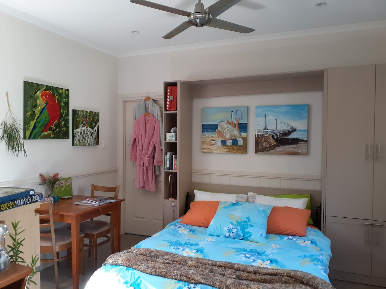 Studio showing queen bed and table for two. Bath robes for guests; local artist original paintings of local features; current magazines and local paper for guests to read along with a selection of novels and 'coffee table' books.