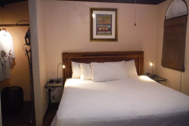 Bedroom with king bed, reading lights, plugs/USB charging station on each side of bed.