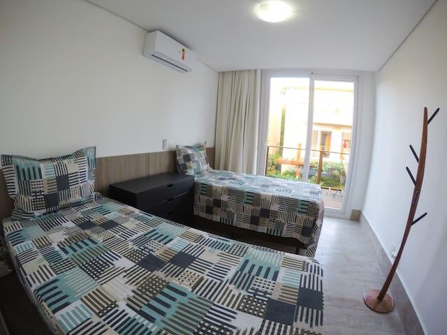 Quarto 2 - Suíte com 2 camas de solteiro e acesso à varanda.