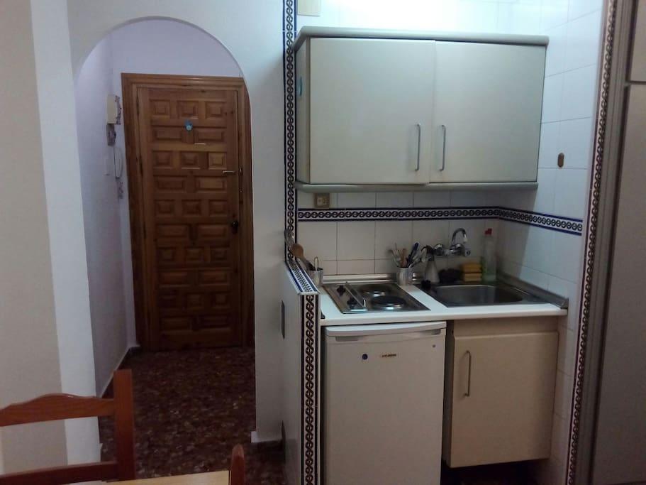 Cocina con nevera, placas eléctricas,  fregadero y armario con enseres de cocina.