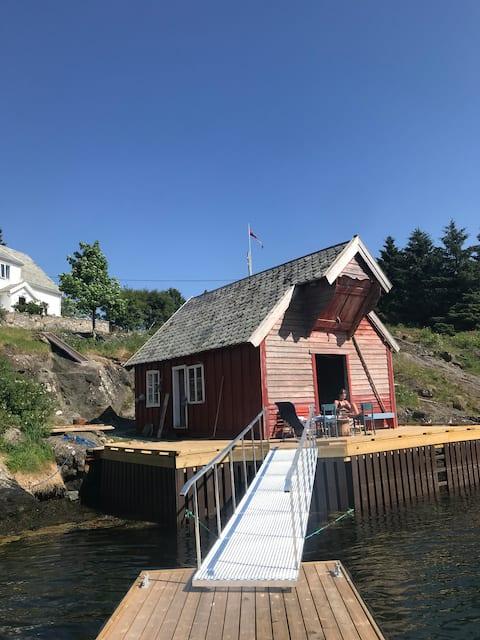 Fin liten orginal hytte i havgapet med båt utleie!