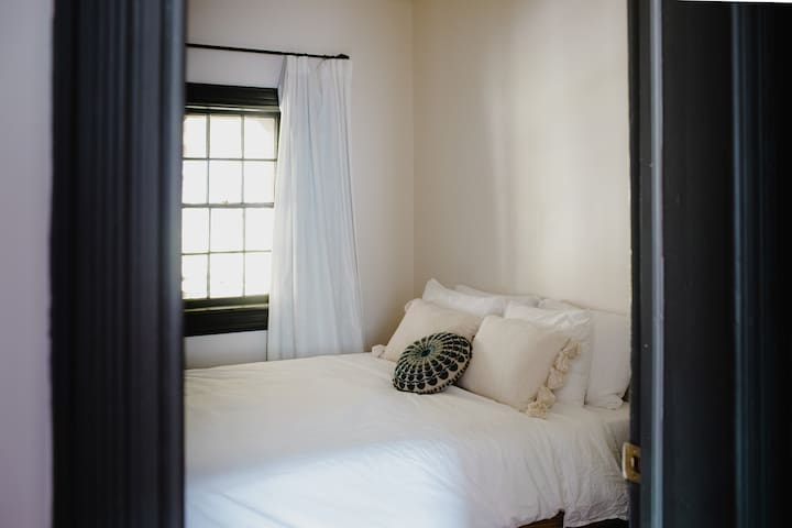 Bedroom with a small closet, hangers, queen-sized bed, and small dresser