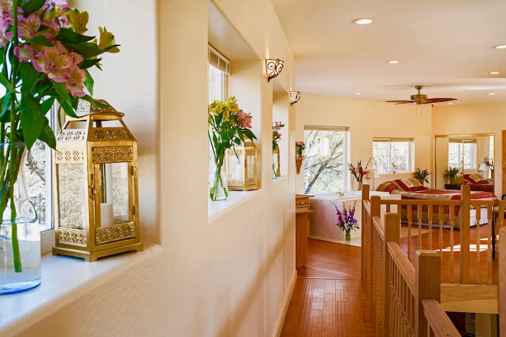 Walking the from the loft bedroom  to the master suite is a pleasant adventure. An executive desk for two is built into a by window at the end of the scenic wooden walkway. The whirlpool tub with a view is on the right.