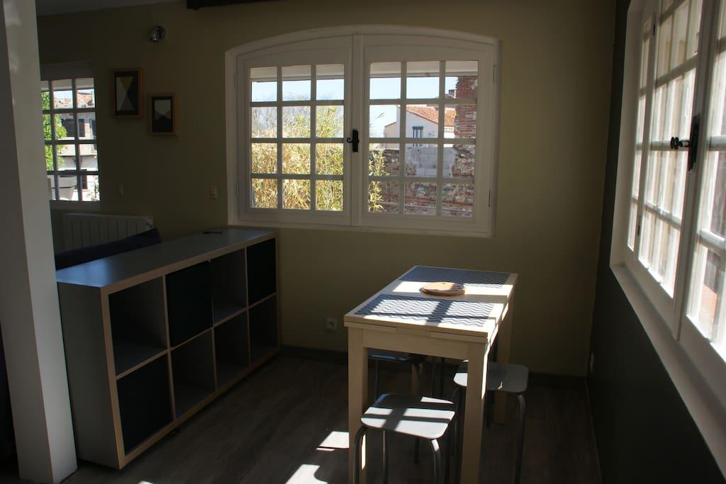 coin repas, pièce très lumineuse (3 fenêtres). Table dépliable pour 4 personnes.