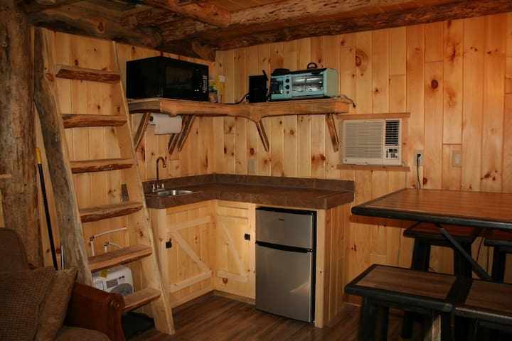 Kitchen equipped with a sink, microwave,refrigerator, griddle, coffee pot,hot plate and crockpot.