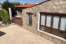 Fachada de la casa y parte del Salón/ Comedor de piedra a vista desde el aparcamiento.