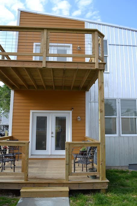 Rear of property. Fenced in back yard. Two decks. Large deck on 2nd floor off of Queen Guestroom. Faces South - Sunny all day!
