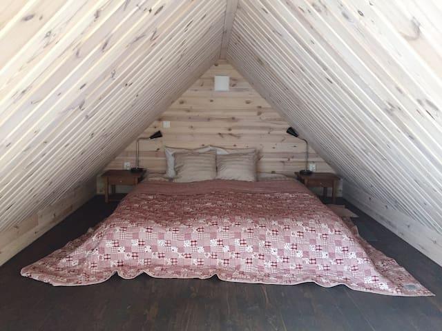 Kingsized bed (2 x 90 cm x 2 m) at the far end of the sleep loft.