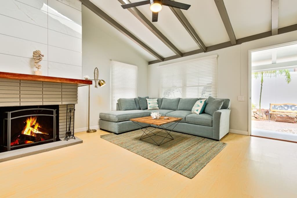 Vaulted ceiling living room with a magnificent fireplace.