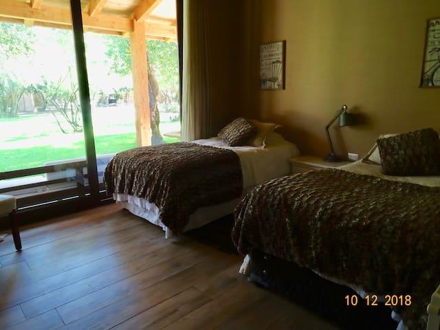Pieza 2 Dos camas + una cama nido, closet y velador central Cortinas BlackOut y salida al jardín.