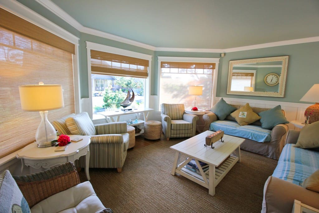Nautical living room with two couches, three arm chairs and beautiful bay windows for ample natural lighting.