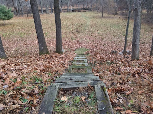 Rustic steps leading to the field and creek.