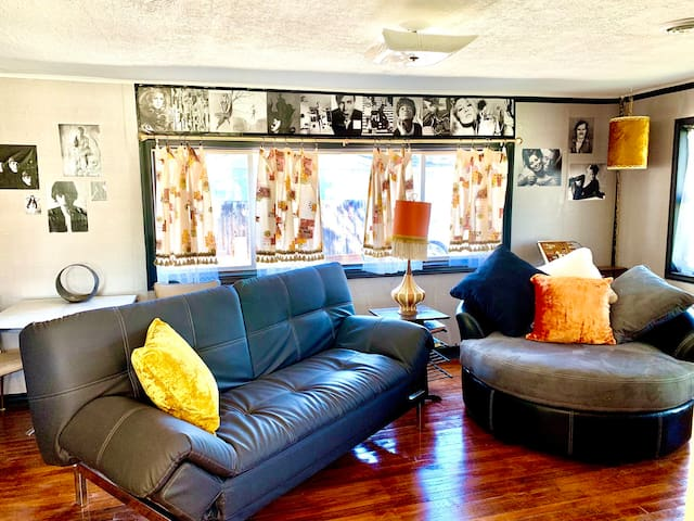 Living room with sofa/sleeper and swivel loveseat. Sixties celebs and custom lampshades, pillows, and drapes.