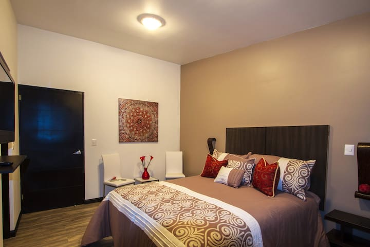 Dormitorio principal con cama Queen, televisor con cable, walking closet, baño privado.