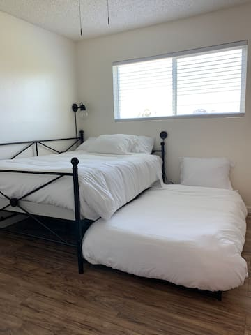 A comfortable full size with a twin size trundle bed topped with memory foam mattresses