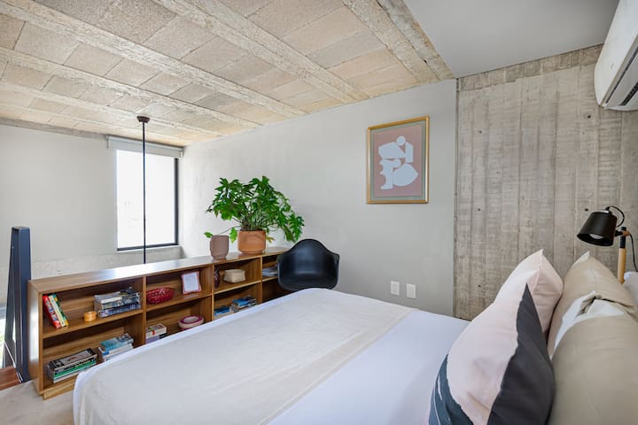 Queen size bed, air conditioning unit, book shelf.