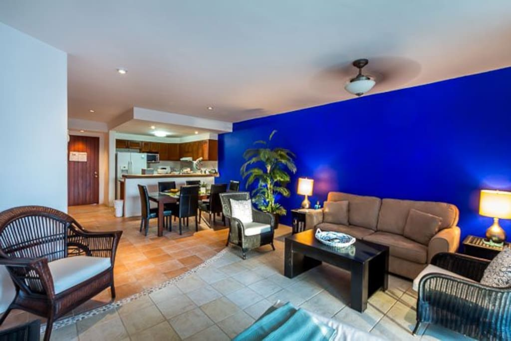 The bright and colorful living area has a comfy couch and bonus pullout sleeper sofa