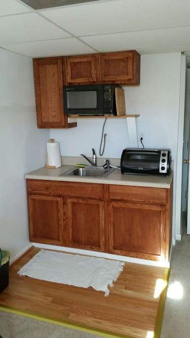 Mini kitchen with microwave, toaster oven, dorm sized fridge. Inside cabinets- George Forman grill, griddle, hot plate to cook on, pots & pans. Dishes, silverware and cooking utensils.