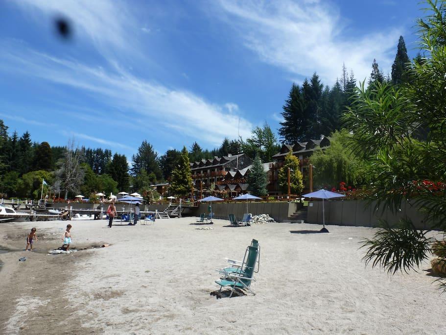 Playa de arena con acceso al lago al fondo el resort y sus jardines