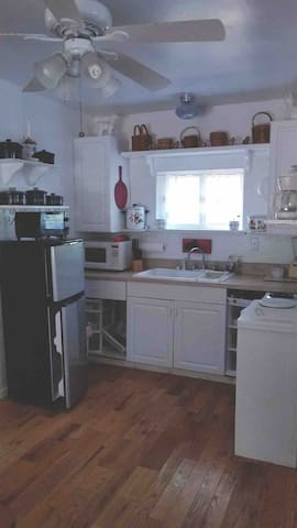 KITCHEN SPACE WITH SMALL REFRIGERATOR/FREEZER, MICROWAVE, COFFEE POT, TOASTER OVEN, BUFFET RANGER WITH TWO BURNERS & A SINGLE BURNER & BLENDER.