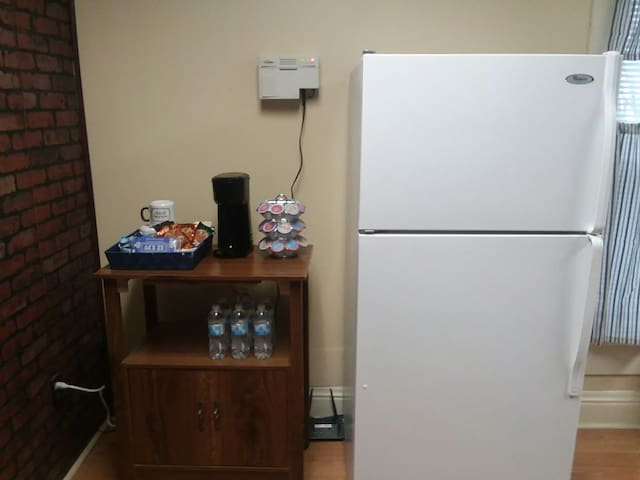 Fridge and drink station. Help yourself to a warm drink, bottle of water, or a bag of popcorn.
