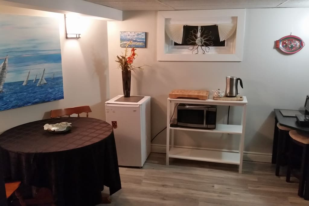 The shared kitchenette includes Fridge, Microwave, Induction stove, coffee maker and toaster oven. Dishes and basic pantry supplies.