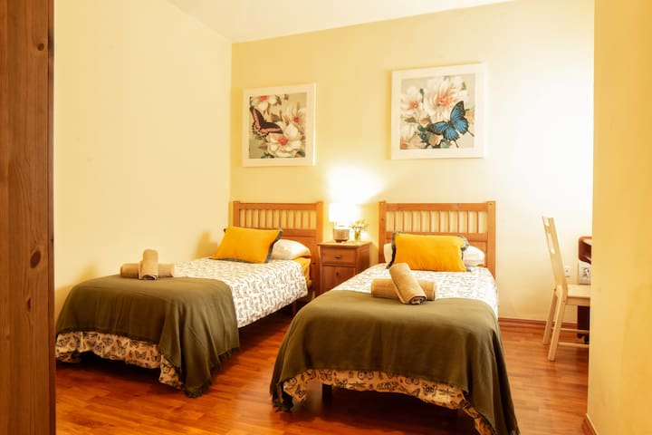 Twin bedroom with two beds and wardrobe space for you things.