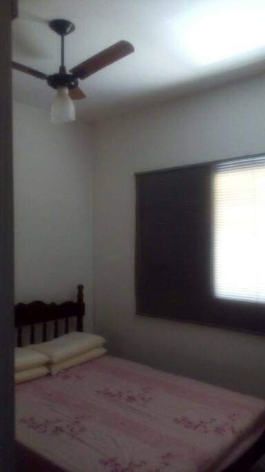 Quarto com cama de casal, guarda-roupa e ventilador de teto