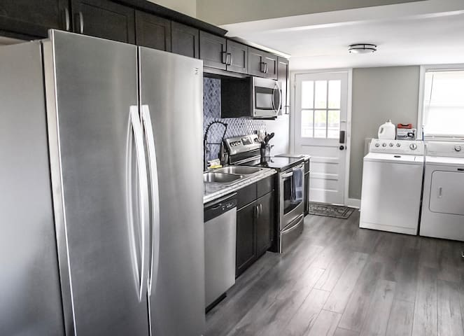 Fully stocked kitchen with dishes, cutting board, knife set, microwave, coffee maker, coffee, cream, sugar, equal and more.