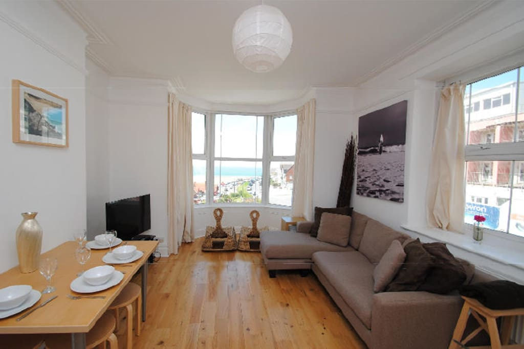 Lounge showing  spacious open plan living room with large plasma, bay window and panoramic view of the sea and sunsets.